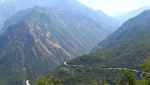 A road traverses through the mountainous Kings Canyon National Park.