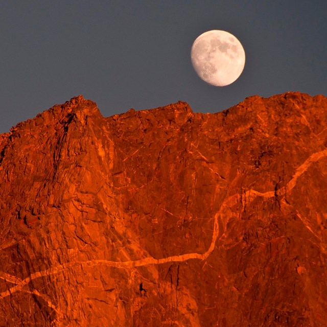 A moonrise over reddish peaks