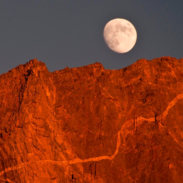 The moon over an alpine peak