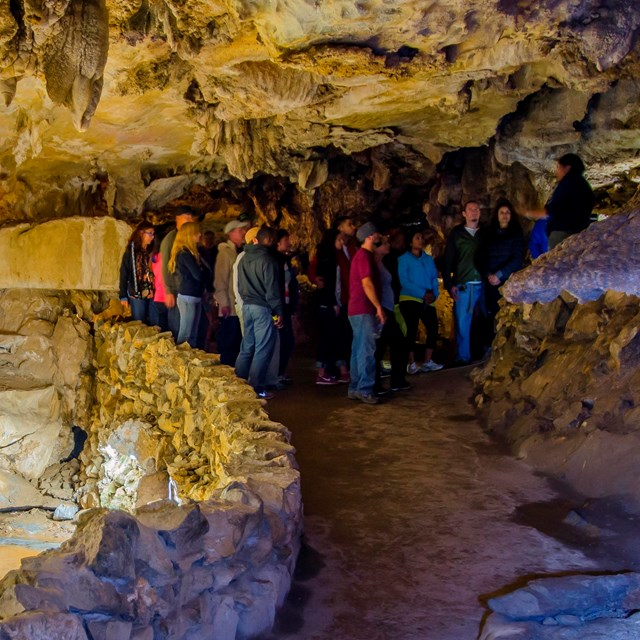 A group of people in a cave room near a stream. Photo by Alison Taggart-Barone.