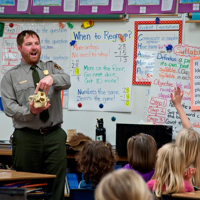 A ranger in the front of a classroom points to a bear skull. One student has raised her hand.