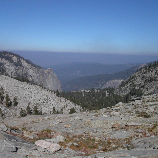 A distant hazy sky with particulate matter forms over Sierra mountains.
