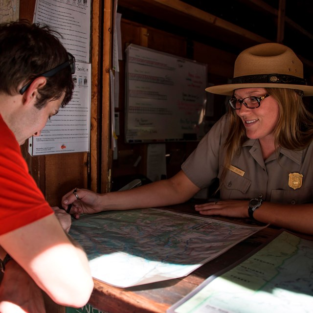 A ranger at a desk talks with a person. Photo by Alison Taggart-Barone.