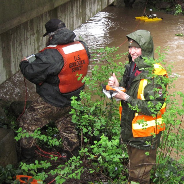Hydrologists measuring the flow of a fast-flowing stream during a storm