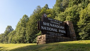 Shenandoah entrance sign on rock frame; blue skies above