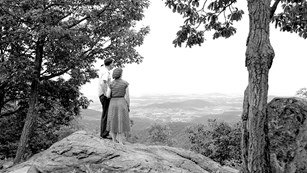 A black and white historical image showing a couple standing on a rock at an overlook