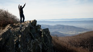 A man stands at the peak of hawksbill mountain.