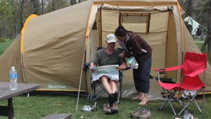 Two people study a map in front of a beige tent.