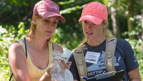 One women holds a water quality sample as a second women records the results on a clipboard,