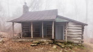 A wooden rustic cabin with a porch, two doors, and a stone chimney is surround by fog in the woods.