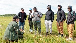 A group of teenage students listen to an education Ranger amongst  the plants of Big Meadows.