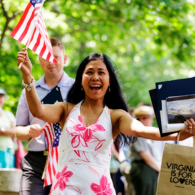Woman holding flag at a naturalization ceremony.