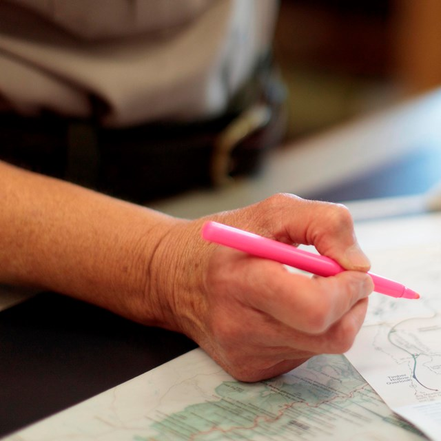 A ranger holding a highlighter on a map.