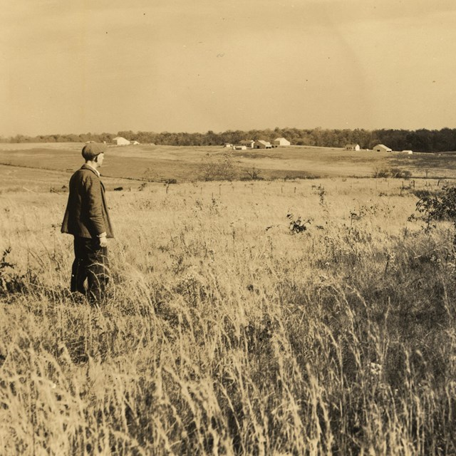A historical image of a man looking across a field.
