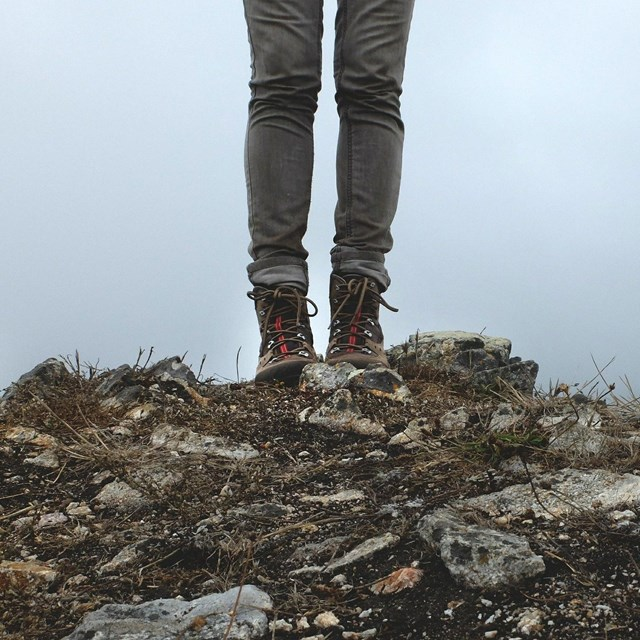 A close-up of a hiker's legs with hiking boots, standing on a rocky viewpoint.