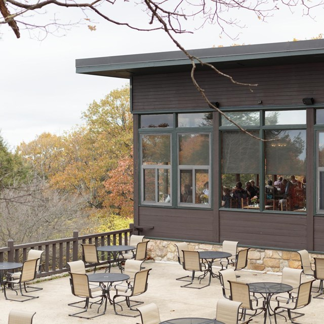 An outdoor seating area adjacent to an indoor restaurant with a view of the valley below.