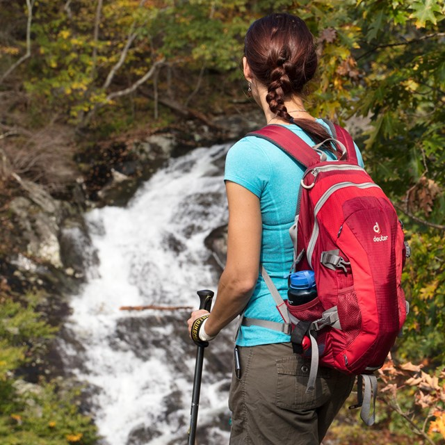 A woman hiker with a red backpack looks out over a waterfall in the distance.