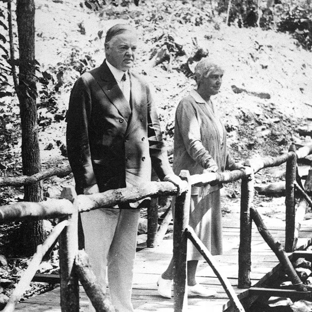 A historic photo of Mr. and Mrs. President Hoover on a bridge in the woods.