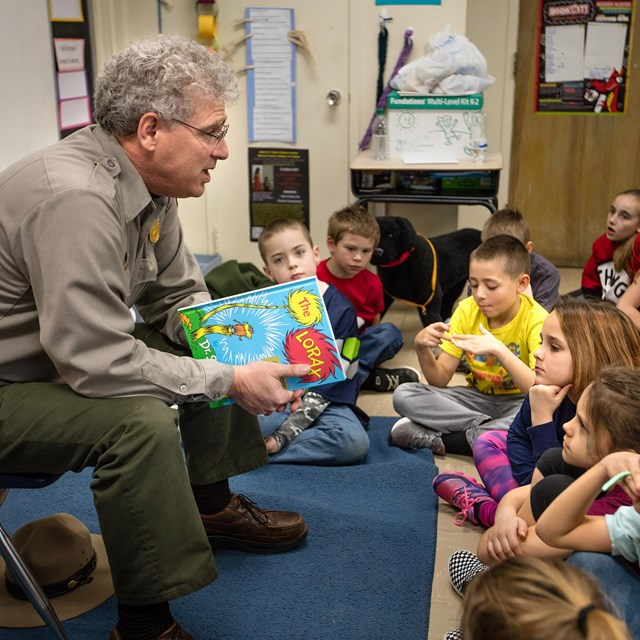A ranger reading to kids in a classroom.
