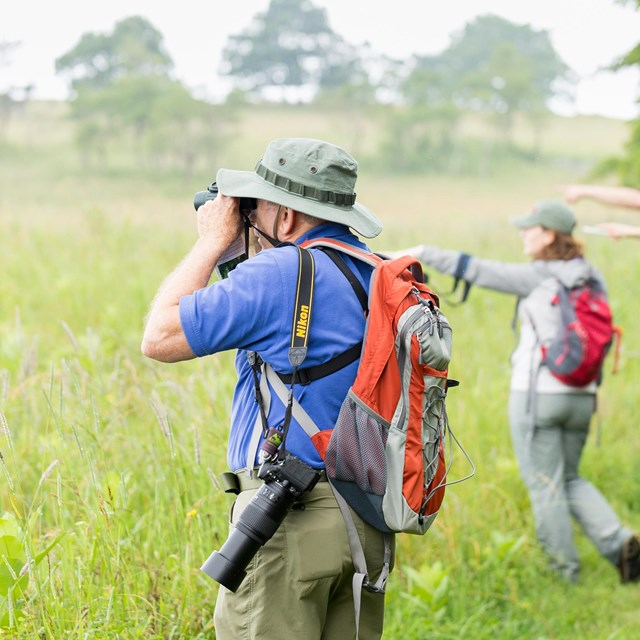 A man with binoculars looking to the distance with people in the background are pointing.