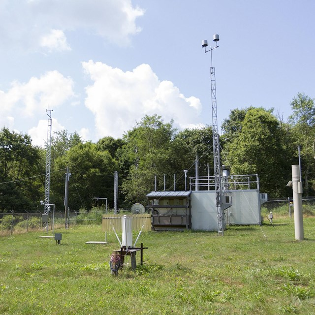 An air quality monitoring station, outdoors, with many scientific instruments scattered about.