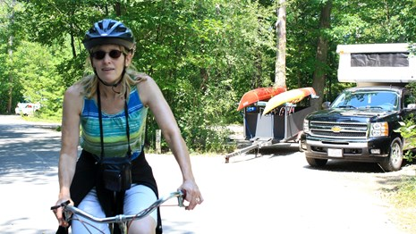 A woman rides her bike past a campsite with kayaks and a pickup camper.