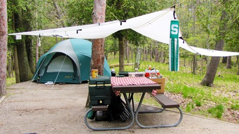 A tent, picnic table with red and white checked cloth, and sun shield make an inviting campsite.
