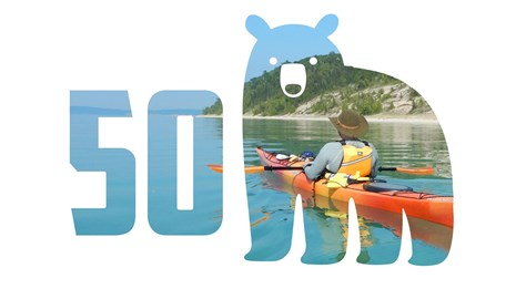 50th anniversary logo of blue bear with sunset over hills