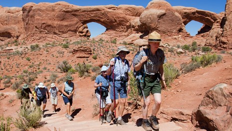 Hikers follow a ranger in Arches National Park.
