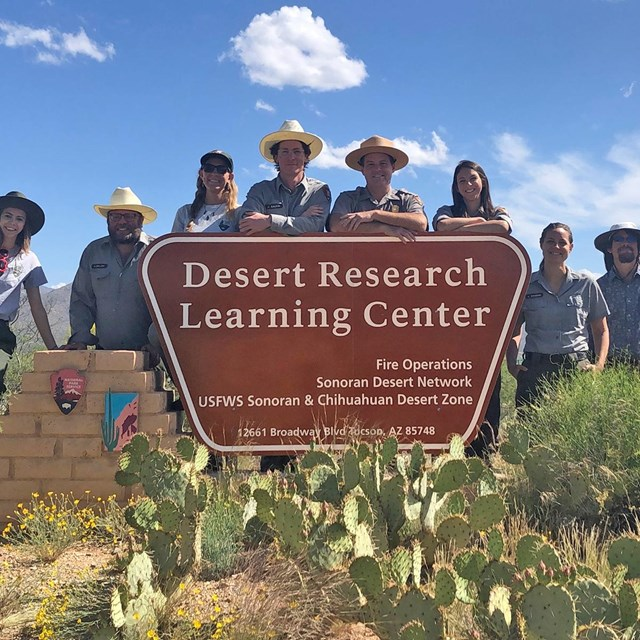 People in NPS uniform gather around a sign for the Desert Research Learning Center