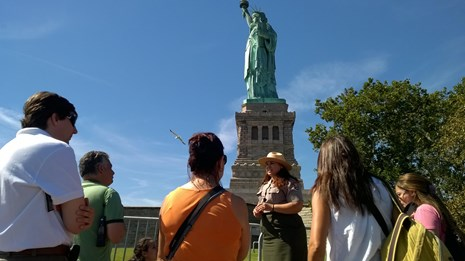 A ranger gives a tour on a bright summer day at the front of Liberty Island.