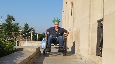A visitor in a wheelchair is moving down a ramp towards the image.