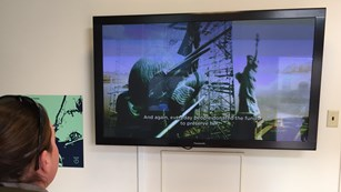 A visitor watching the informational video on the Statue of Liberty with open captions.