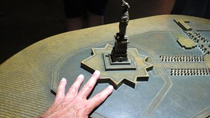 A hand touching a metal model of the Statue of Liberty.