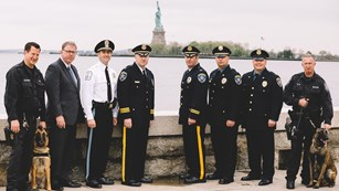Park Police Officers and their K-9's on Ellis Island with the Statue in the background.