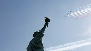 Military planes fly in formation above the Statue of Liberty.