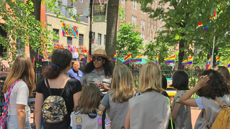 Park Ranger talking with group of young visitors inside a park surrounded by rainbow flags