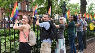 Five visitors and one park ranger standing next to an iron fence as they post rainbow flags.