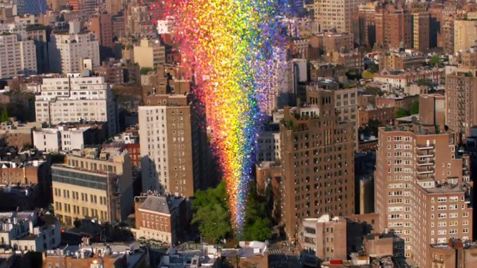 The city and a multi-colored rainbow shooting upward from a cluster of trees in the center.