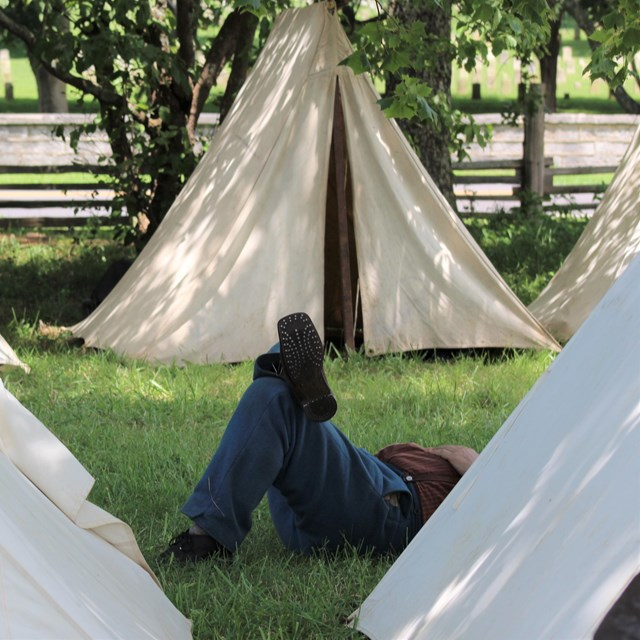 A Union Soldier laying down among white canvas tents.