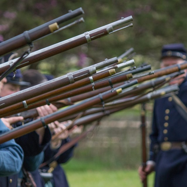A row of soldiers hold muskets in the air with a Union soldier looking on in the background.