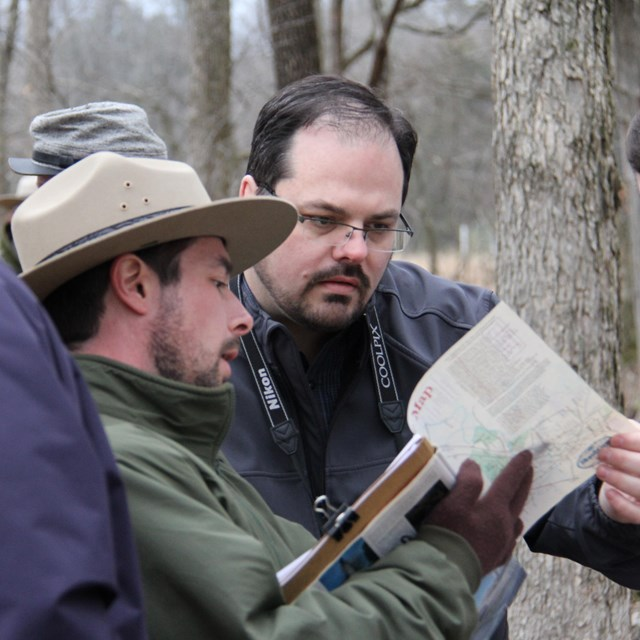 A ranger points to a map while visitors look on.