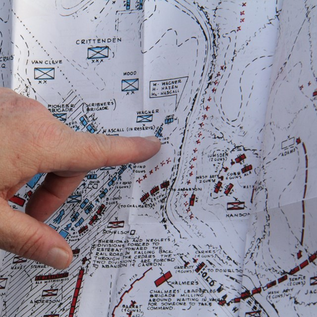 A finger points to a spot on a map.