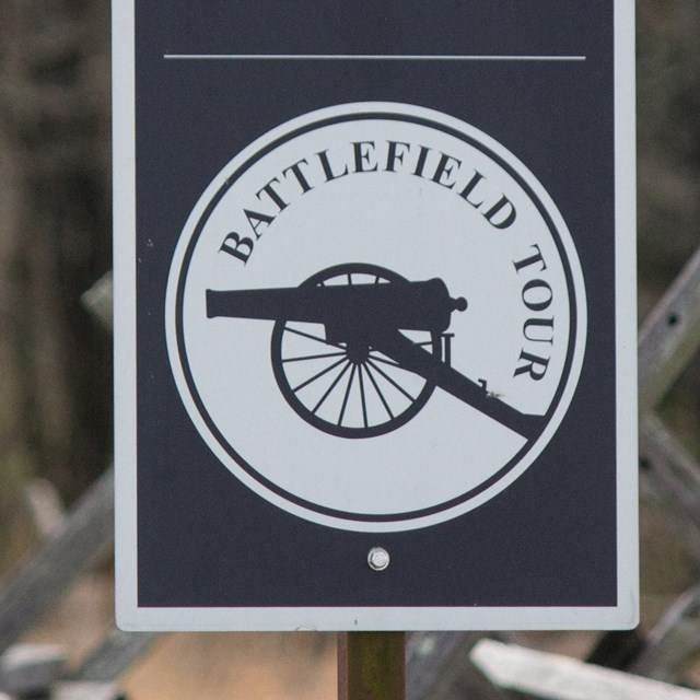 A black and white sign that says Battlefield Tour with the picture of a Civil War cannon in profile.