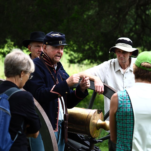 Man dressed as Civil War soldier speaks to visitors in front of cannon