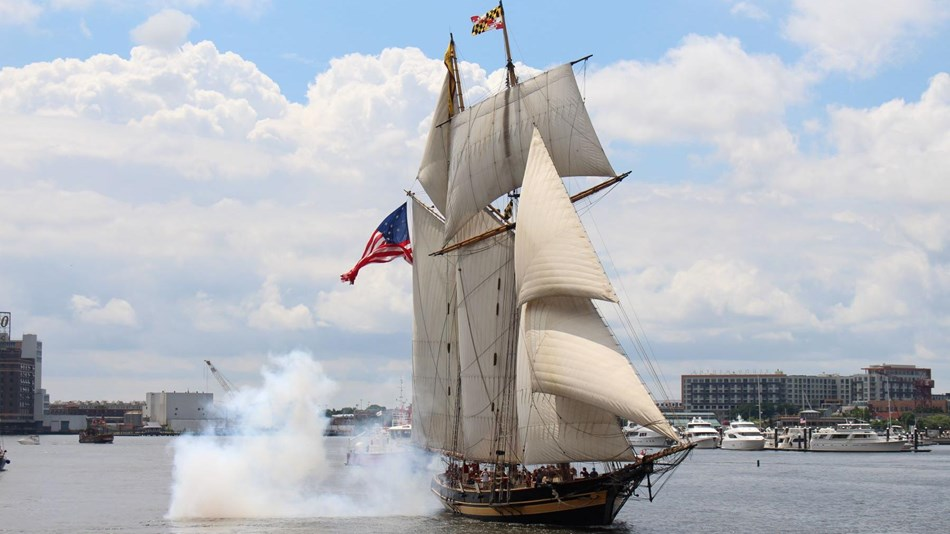 Photograph of a tall ship sailing after firing a cannon.