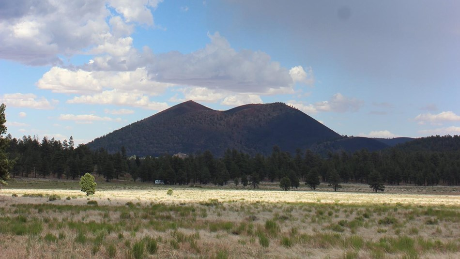 open meadow and volcanic cinder cone under rainy skies