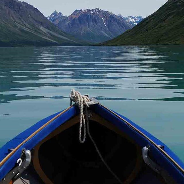 The bow of a kayak pointing toward the mountains.