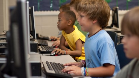 Photo of several children on computers. CC0