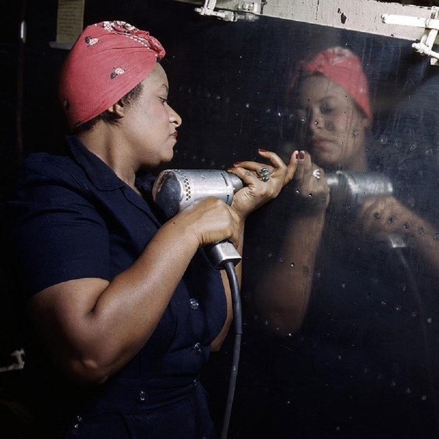 Woman riveting the side of a plane.